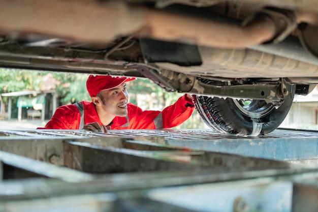 Männlicher auto-reiniger, der die rote uniform trägt, schaut unter das auto, während das auto im autosalon gewaschen wird