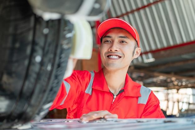 Männlicher auto-reiniger trägt rote uniform und lächelnden hut, während er reifen im autosalon wäscht