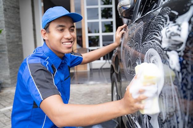 Männlicher auto-reinigungsservice-arbeiter, der schwarzes auto wäscht