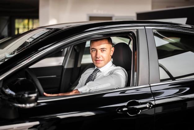 Männlicher autohändler der vorderansicht innerhalb des autos