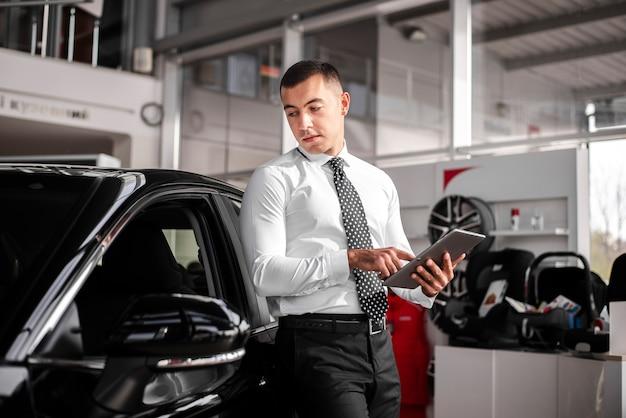 Männlicher autohändler der vorderansicht mit tablette