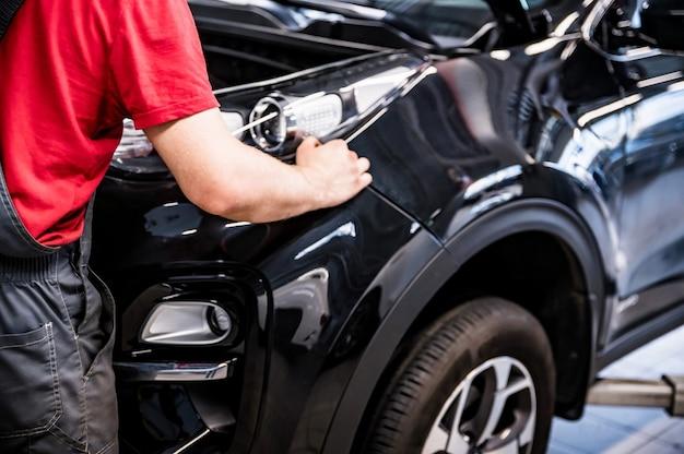 Männlicher automechaniker am autosalon übergibt schwarze geschäftsklasse des autos am autoservice