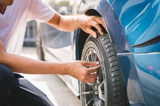 Männlicher automobiltechniker der nahaufnahme, der reifenventil-stickstoffkappe für reifeninflation entfernt