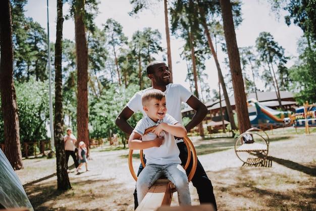 Männlicher babysitter und kind auf spielplatz spielen wippe.