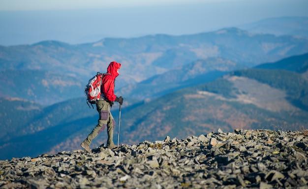 Männlicher backpaker, der auf die felsige spitze des berges geht