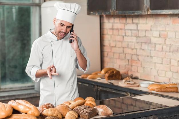 Männlicher bäcker, der auf dem mobiltelefon steht im bäckereigestikulieren spricht