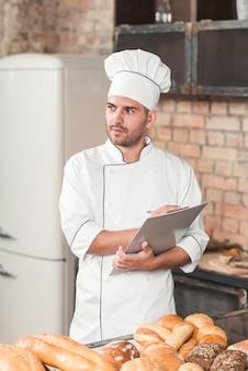 Männlicher bäcker, der auf klemmbrett mit gebackenen broten auf küche worktop schreibt