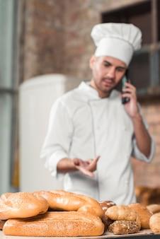 Männlicher bäcker, der auf mobiltelefon hinter dem brotlaib spricht