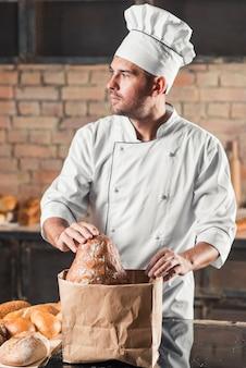 Männlicher bäcker, der brot in der braunen papiertüte hält