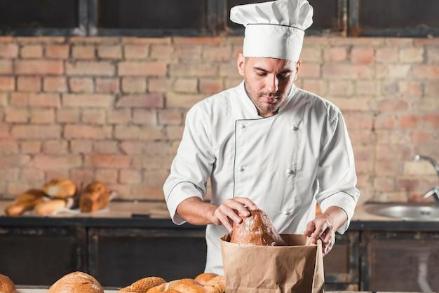 Männlicher bäcker, der brote in der papiertüte schaut