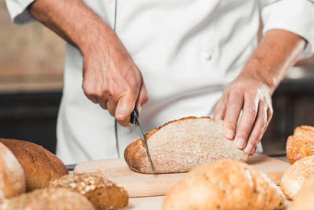 Männlicher bäcker, der brotlaib auf hackendem brot schneidet