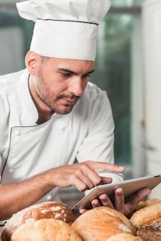 Männlicher bäcker, der digitale tablette mit broten verwendet