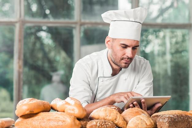 Männlicher bäcker, der digitale tablette mit vielen broten auf tabelle verwendet