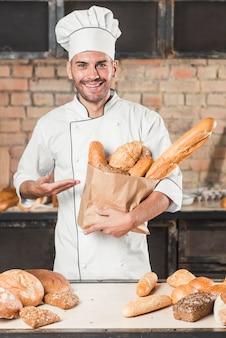 Männlicher bäcker, der eine braune papiertüte mit frisch gebackenem köstlichem brot hält