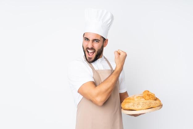 Männlicher bäcker, der eine tabelle mit mehreren broten lokalisiert auf weißer wand hält, die starke geste macht