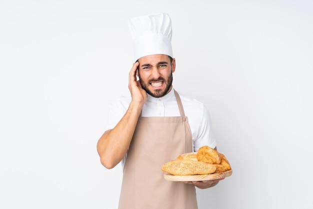 Männlicher bäcker, der einen tisch mit mehreren broten an der weißen wand unglücklich und mit etwas frustriert hält.