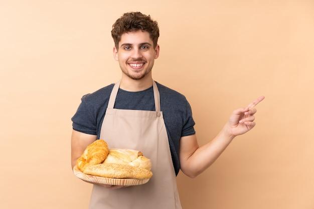 Männlicher bäcker, der einen tisch mit mehreren broten auf beige wand hält, der finger zur seite zeigt