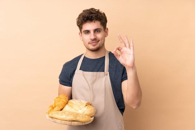 Männlicher bäcker, der einen tisch mit mehreren broten auf beige wand hält, die ein ok-zeichen mit den fingern zeigt