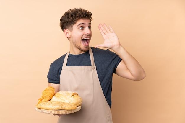 Männlicher bäcker, der einen tisch mit mehreren broten auf beige wand hält, die mit offenem mund schreien