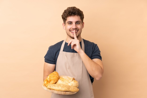 Männlicher bäcker, der einen tisch mit mehreren broten auf beige wand hält, die schweigegeste tut