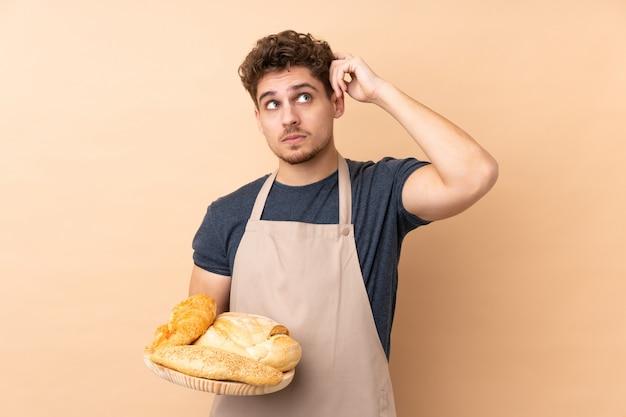 Männlicher bäcker, der einen tisch mit mehreren broten auf beige wand hält, die zweifel und mit verwirrtem gesichtsausdruck hat