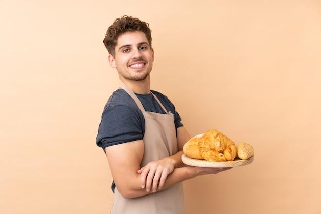 Männlicher bäcker, der einen tisch mit mehreren broten auf beige wand lachend hält