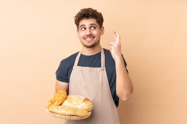 Männlicher bäcker, der einen tisch mit mehreren broten auf beige wand mit den fingern kreuzend hält