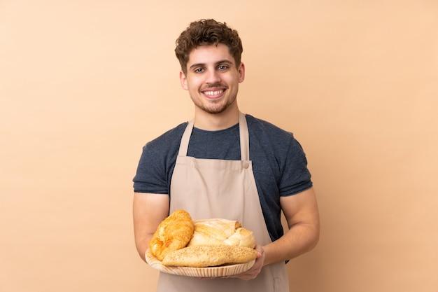Männlicher bäcker, der einen tisch mit mehreren broten auf beigem wand applaudierend hält