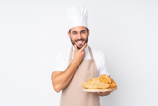 Männlicher bäcker, der einen tisch mit mehreren broten auf der weißen wand lachend hält