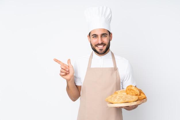 Männlicher bäcker, der einen tisch mit mehreren broten auf weißer wand hält, der finger zur seite zeigt