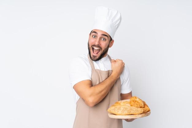 Männlicher bäcker, der einen tisch mit mehreren broten auf weißer wand hält, die einen sieg feiert