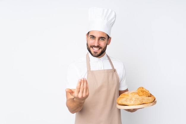 Männlicher bäcker, der einen tisch mit mehreren broten auf weißer wand hält, die einlädt, zu kommen