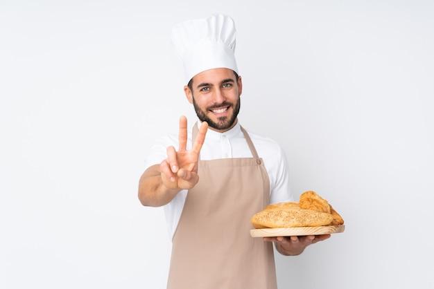 Männlicher bäcker, der einen tisch mit mehreren broten auf weißer wand hält, die lächelt und siegeszeichen zeigt