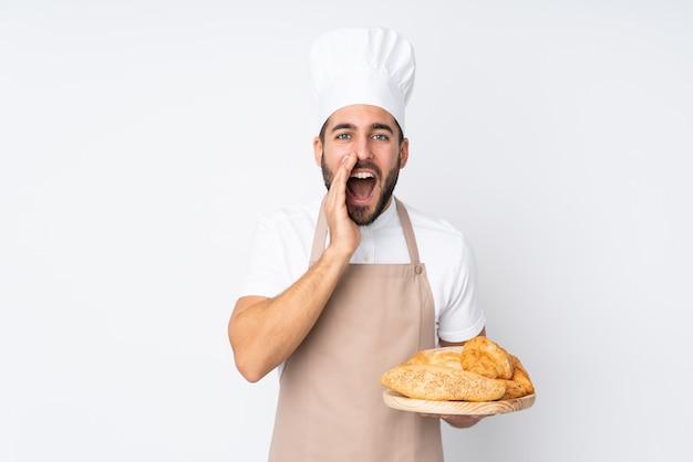 Männlicher bäcker, der einen tisch mit mehreren broten auf weißer wand hält, die mit offenem mund schreien