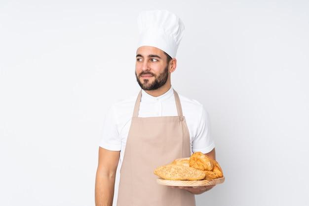 Männlicher bäcker, der einen tisch mit mehreren broten auf weißer wand hält und zur seite schaut