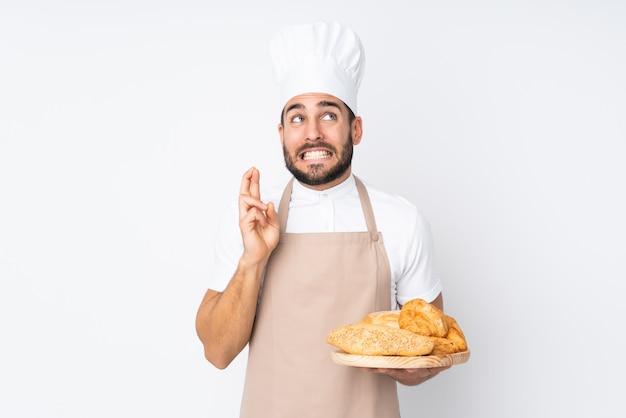 Männlicher bäcker, der einen tisch mit mehreren broten auf weißer wand mit den fingern kreuzend hält