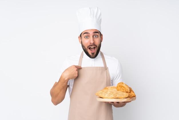 Männlicher bäcker, der einen tisch mit mehreren broten auf weißer wand mit überraschtem gesichtsausdruck hält