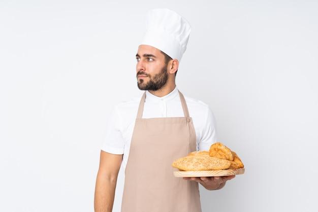 Männlicher bäcker, der einen tisch mit mehreren broten auf weißer wand schaut seite hält