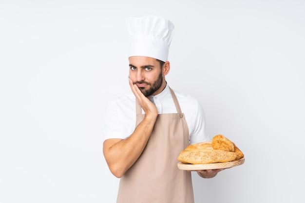 Männlicher bäcker, der einen tisch mit mehreren broten auf weißer wand unglücklich und frustriert hält