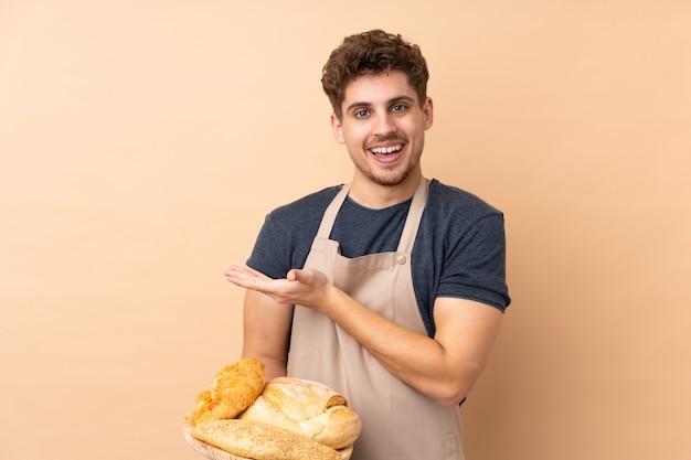 Männlicher bäcker, der einen tisch mit mehreren broten hält, die auf beige wand isoliert sind, die hände zur seite ausdehnt, um einzuladen, zu kommen
