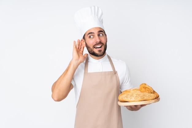 Männlicher bäcker, der einen tisch mit mehreren broten hält, die auf weißer wand lokalisiert hören1,