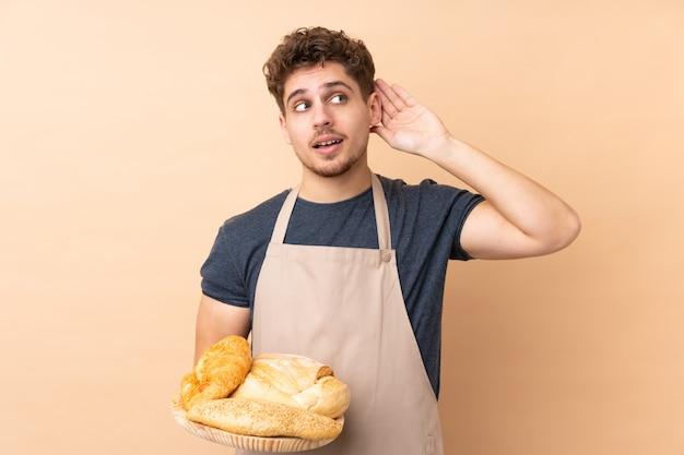 Männlicher bäcker, der einen tisch mit mehreren broten lokalisiert auf beige wand hält, die etwas hören