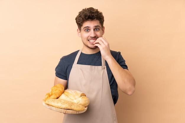 Männlicher bäcker, der einen tisch mit mehreren broten lokalisiert auf beige wand nervös und verängstigt hält