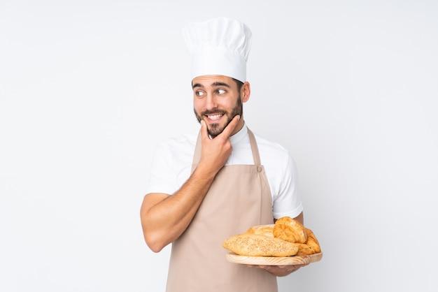 Männlicher bäcker, der einen tisch mit mehreren broten lokalisiert auf weißer wand hält, die eine idee denken