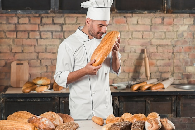 Männlicher bäcker, der gebackenes brotlaib riecht