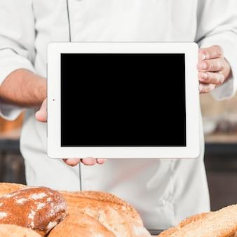 Männlicher bäcker, der leere digitale tablette mit gebackenen broten hält