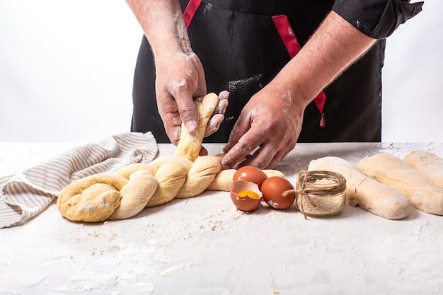 Männlicher bäcker, der traditionelles jüdisches challa-brot macht. kochschritt