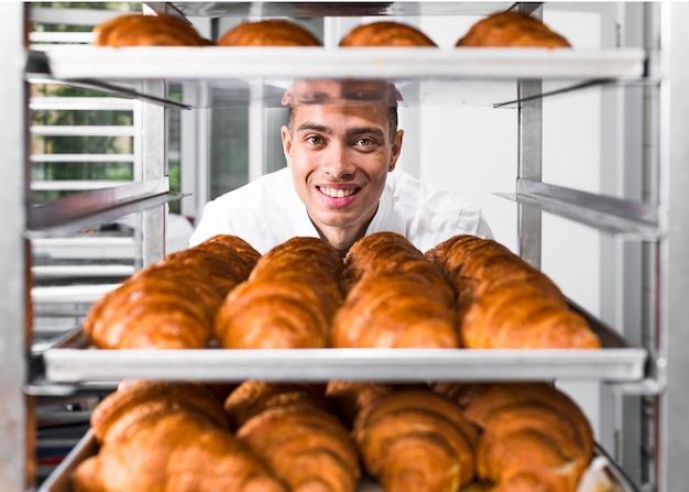 Männlicher bäcker, der voll hinter den regalen mit frischem gebackenem hörnchen steht