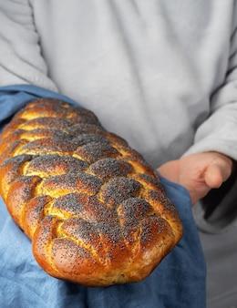 Männlicher bäcker hält ein traditionelles gebackenes süßes brot