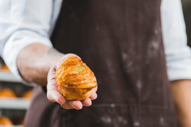 Männlicher bäcker im schutzblech, das frisch gebackenen süßen blätterteig hält